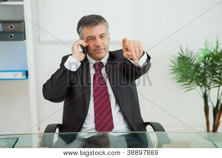 Businessman phoning and pointing at his desk in his office