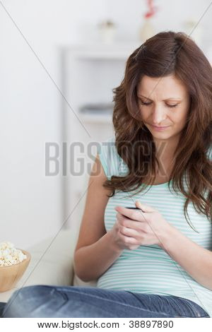 Woman sitting using a mobile phone in a living room