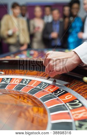 Dealer dropping ball into roulette wheel in casino