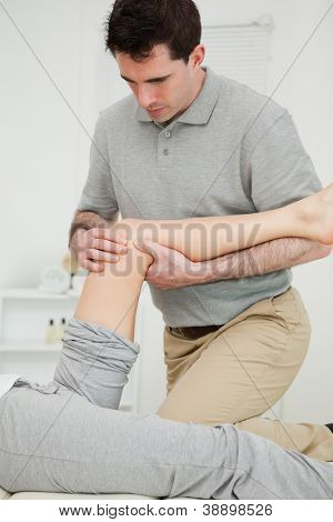 Serious physiotherapist looking at the knee of a patient in a room