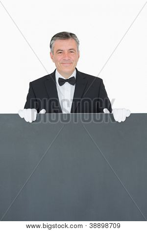 Smiling waiter standing behind blank grey sign