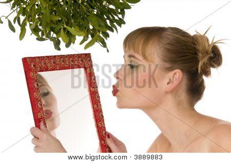 Modelo nua, beijando-se em um espelho sob o visco