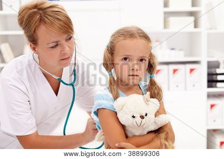 Little girl at the doctor - health professional checking her with stethoscope