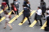 stock photo of commutator  - Overhead View Of Commuters Crossing Busy Hong Kong Street - JPG