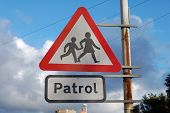 School Crossing Patrol Sign Attached To A Rusty Pole With A Blue Sky Background. poster