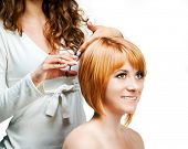 pic of barbershop  - Young woman barber makes hairstyle for a girl isolated on white background - JPG