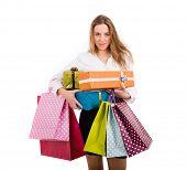 Постер, плакат: Шопоголика молодая женщина держащая подарки и shooping мешки на белом фоне
