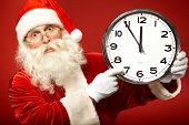 Photo of stunned Santa holding clock showing five minutes to midnight