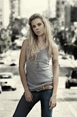 picture of wife-beater  - Young female model in grey wife beater standing against vintage aged city background - JPG