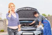Smiling careless female talking on a mobile phone while in the background mechanic is checking her c