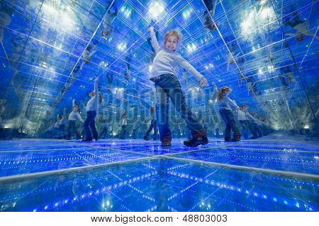 Smiling little girl standing in a mirrored room and spread her arms out to the side