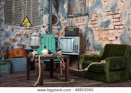 Old armchair, television, radio and table with samovar in very old house.