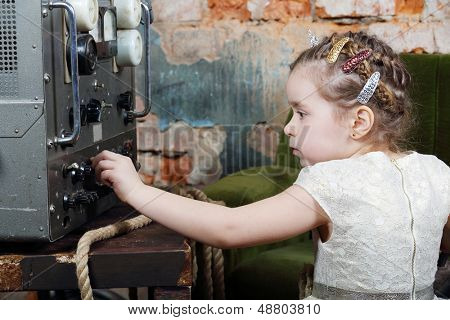 Little cute girl configures power source to radio receiver in very old house.
