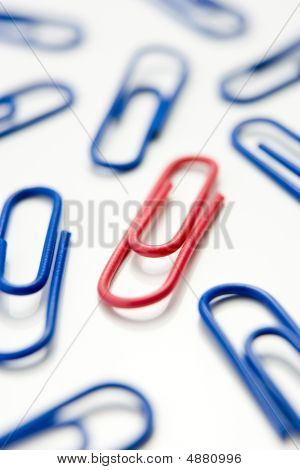 One Red Paperclip Amid Blue Paperclips