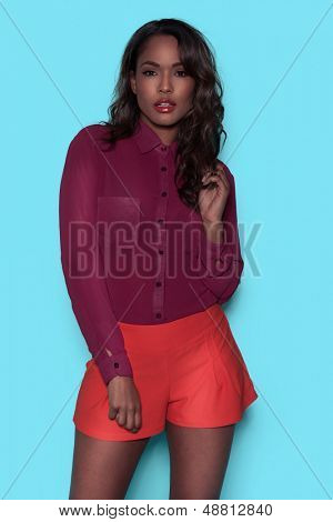 Beautiful young African American model in summer shorts standing looking at the camera with her hand to a lovely long wavy hair