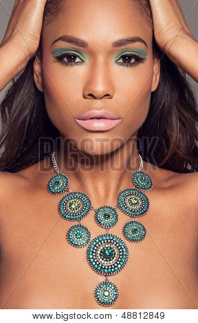 Close up head portrait of a beautiful African fashion model wearing a striking ethncs necklace posing with her hands to her hair