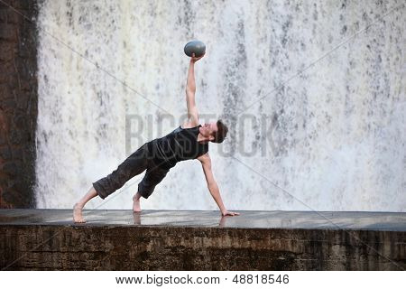 Fit white man exercising with elliptical ball on concrete footbridge at the waterfall
