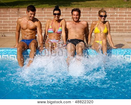 Attractive young people having summer fun by outdoor swimming pool, smiling.
