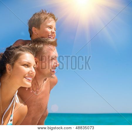 Happy Young Family with Little Child Having Fun at the Beach. Joyful Family. Travel and Vacation Concept. Summer Holidays