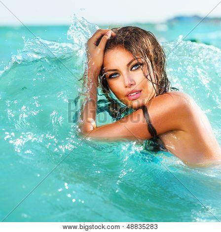Beleza modelo Sexy garota nadando e posando no mar. Linda mulher relaxando na água azul-turquesa.