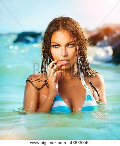 Beauty Sexy Model Girl Swimming and Posing in the Sea. Beautiful Woman Relaxing in turquoise Water. Sensual Girl enjoying the ocean