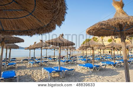 Sandy Beach With Straw Umbrellas And Sunbeds