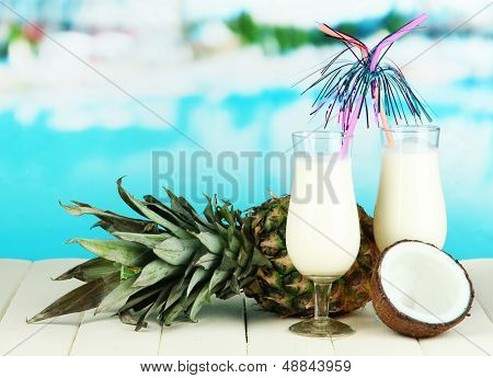 Pina colada drink in cocktail glasses, on bright background