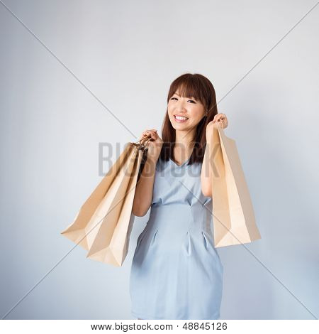 Shopping woman holding shopping bags looking at camera on blue background. Beautiful young Asian shopper smiling happy.