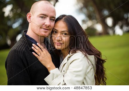 Close up portrait of a young attractive romantic couple, caucasian man, asian woman, in a beautiful outdoor park garden