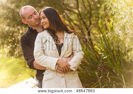 Romantic young couple portrait, asian woman, caucasian man, hugging tenderly in a park with a beautiful sunlight