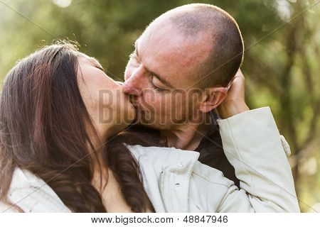 Romantic young couple, asian woman caucasian man, kissing tenderly in outdoor environment
