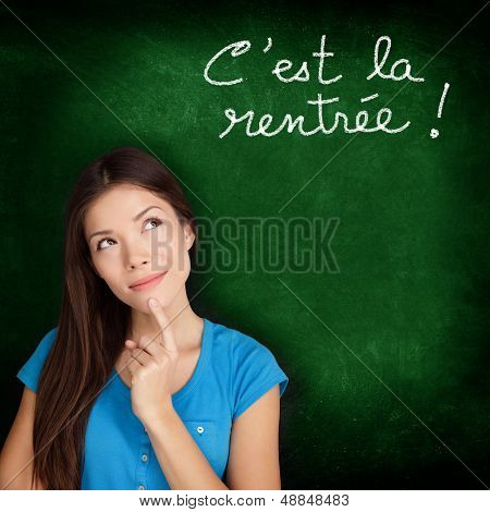 C'est la Rentree Scolaire - French college university student woman thinking Back to School written in French on blackboard by female on green chalkboard. French language at college or high school.
