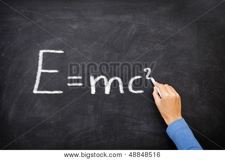 physics science formula equation blackboard, E=mc�². EMC2 written on chalkboard by science teacher or student in class.