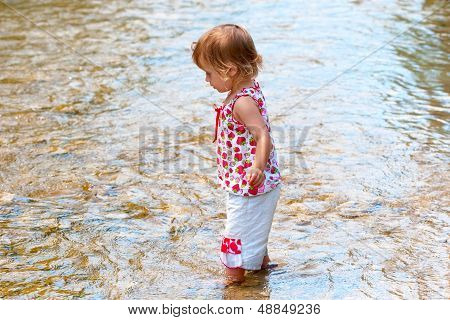 Small Child Play On The Shallow Water