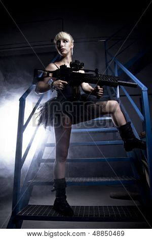 Sexy blonde young, holding a machinegun in an industry area