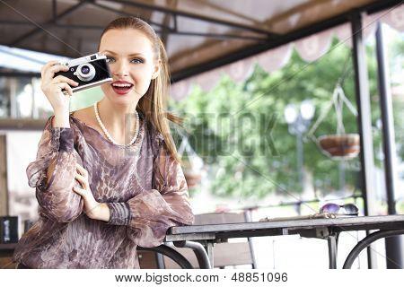 Close-up portrait  girl with a retro photocamera