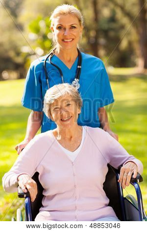 smiling medical nurse with disabled patient outdoors