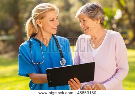 caring caregiver and senior patient outdoors