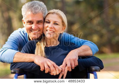 smiling mid age man and disabled wife outdoors