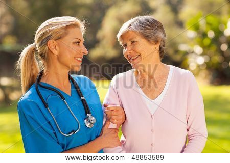 caring nurse talking to senior woman outdoors