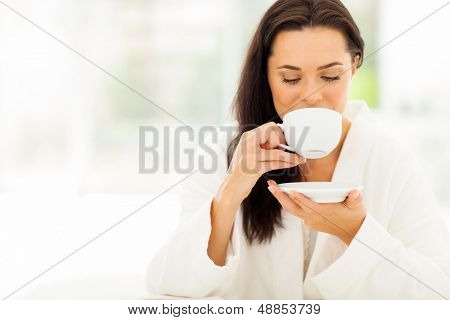 attractive woman in bathrobe drinking coffee in bedroom