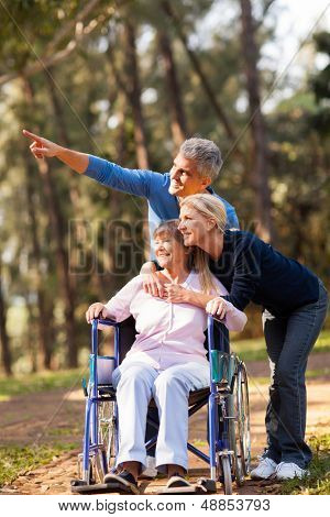 loving mid age couple taking senior mother for a walk outdoors