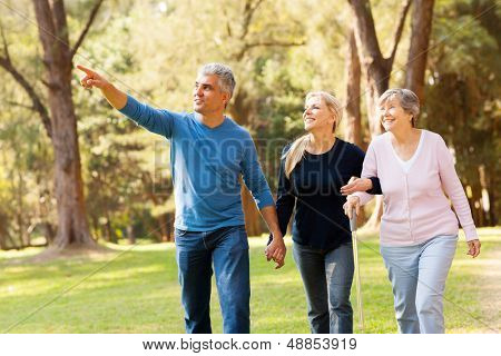 cheerful middle aged couple taking elderly mother for a walk in forest