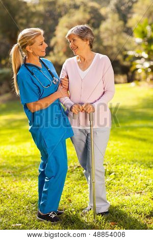 friendly middle aged caregiver talking to senior woman outdoors