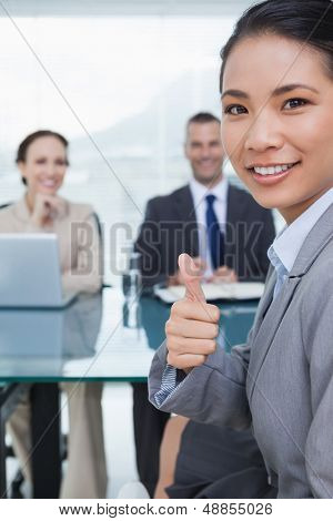 Young pretty applicant in bright office showing thumb up after obtaining the job