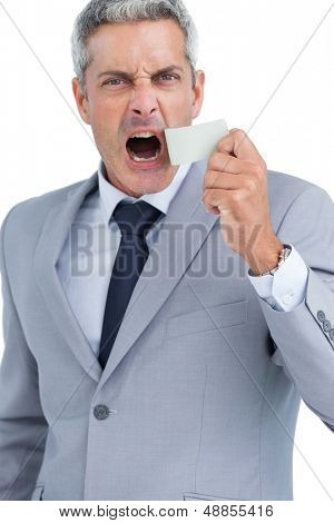 Businessman ripping off duct tape from mouth on white background