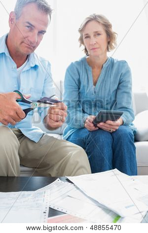 Husband cutting credit card in half with wife with bills on the table at home in the living room