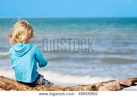Young Child Sitting At The Beach
