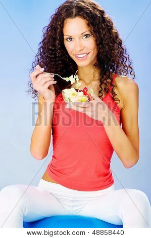 Women Seating On Blue Pilates Ball Holding Fresh Salad On Plate