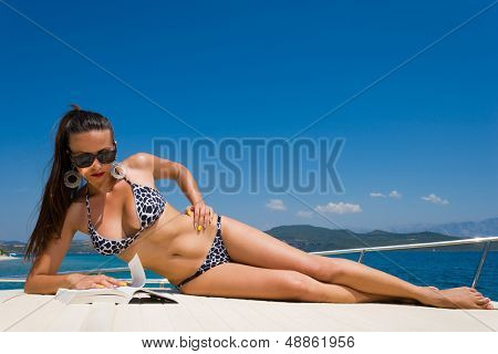 Young woman in bikini reading a book on her private yacht